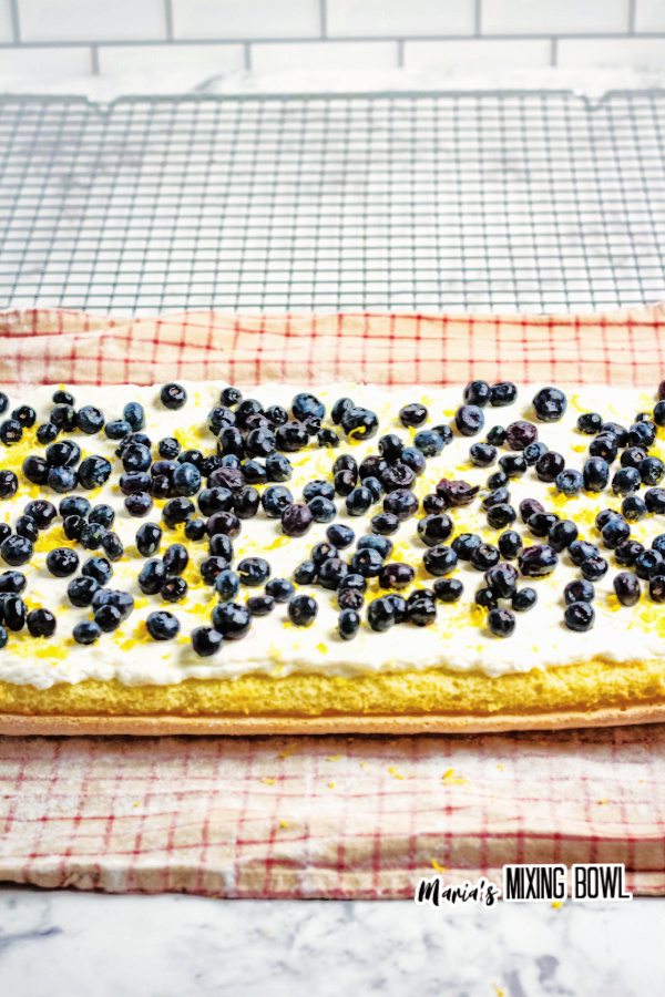 Lemon cake sheet topped with cream cheese mix and blueberries