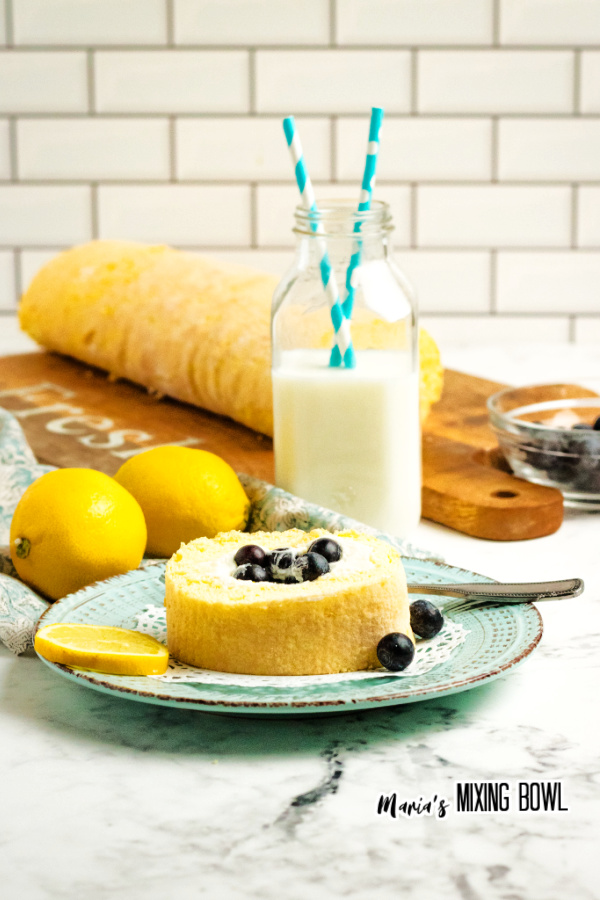 Slice of lemon blueberry cake roll on plate with glass of milk in background