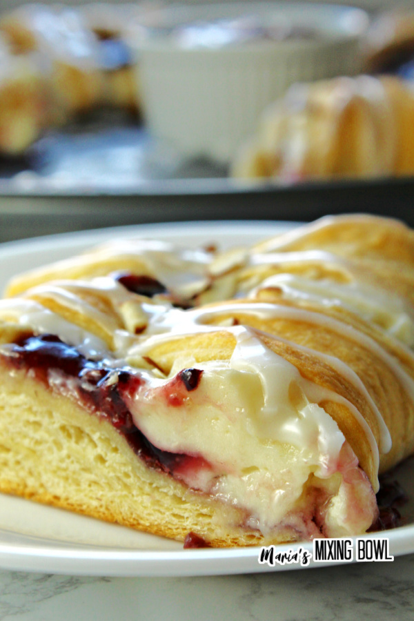 Closeup shot of slice of raspberry cream cheese crescent ring on white plate