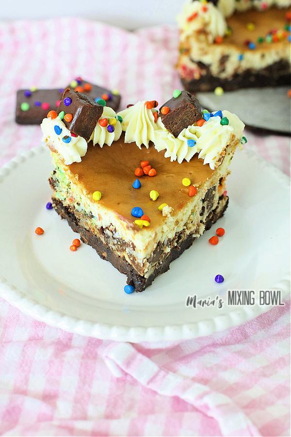 Slice of cosmic brownie cheesecake on white plate