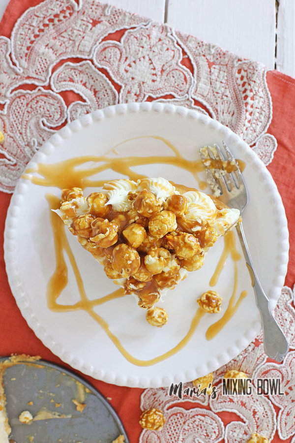 Overhead shot of slice of caramel corn cheesecake with fork on plate