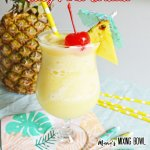 Pina Colada in a fancy glass with cherry and pineapple garnish whole pineapple in background