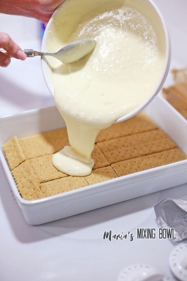 Batter being poured from a bowl over graham crackers in baking dish
