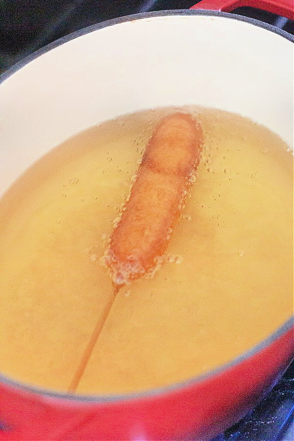 Corn dog being fried in oil