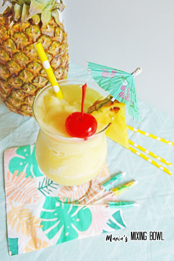 cherry and pineapple, umbrella atop a pina colada with pineapple in background