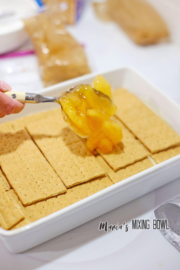 Spooning apple pie filling over graham crackers