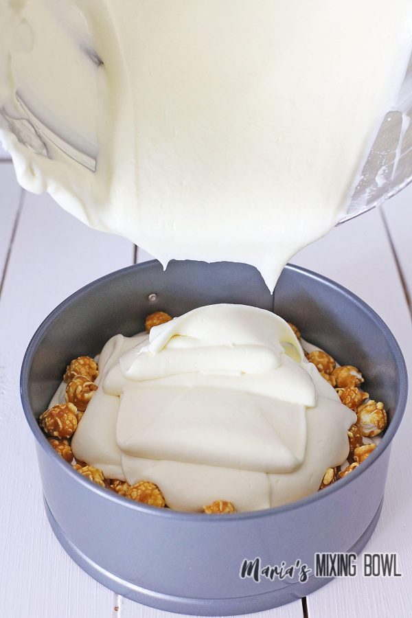 Pouring second layer of cheesecake into springform pan