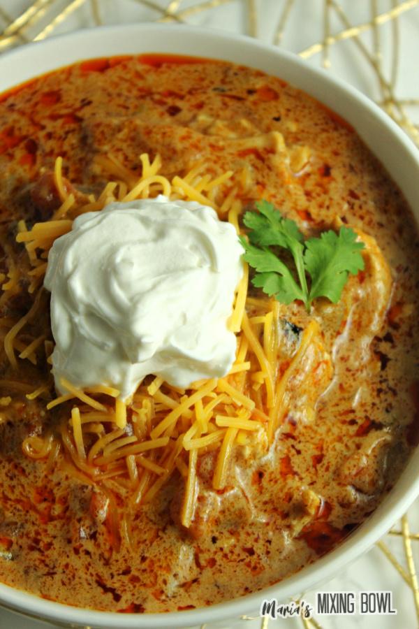 fajita soup with sour cream in a white bowl