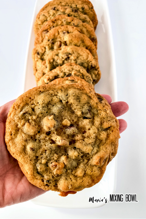Hand holding cookie above platter with more copycat doubletree chocolate chip cookies