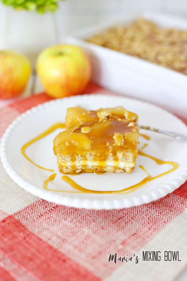 Slice of caramel apple icebox cake on white plate with icebox cake in baking dish in background