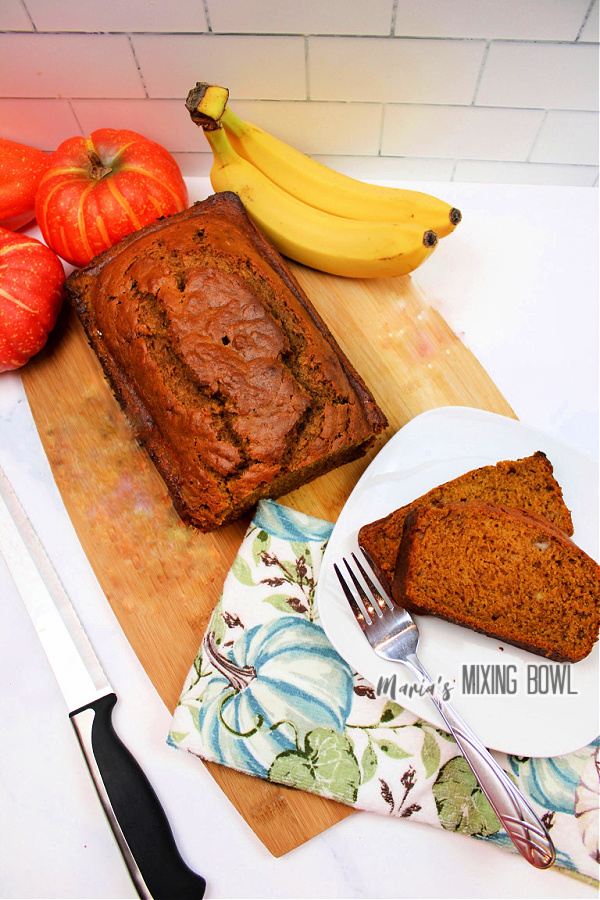 Overhead shot of pumpkin spice banana bread loaf next to slices of banana bread on white plate