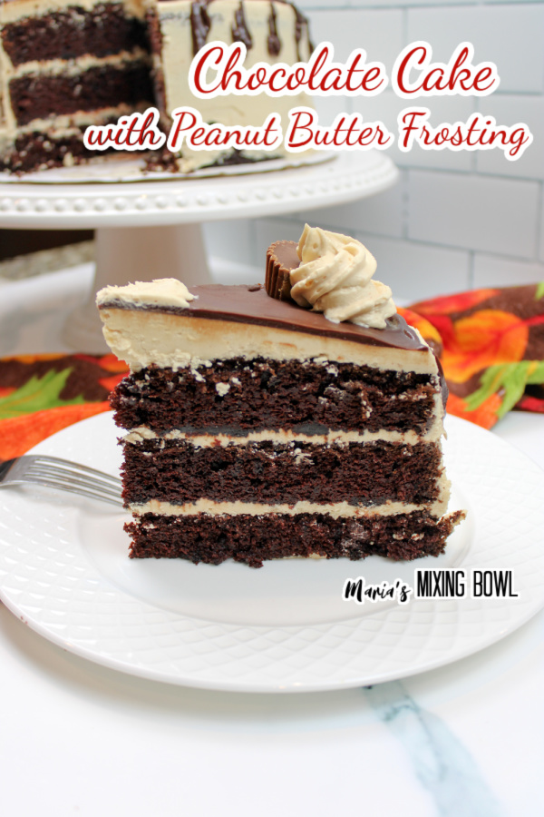 Chocolate cake with peanut butter frosting on plate with more cake on cake stand in background