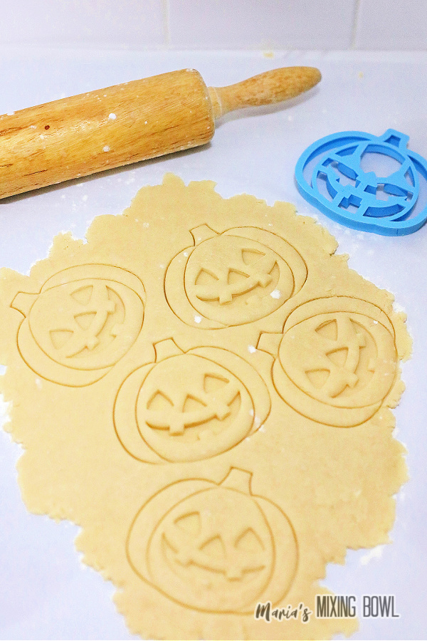 Cookie dough rolled out with pumpkin shapes cut into it