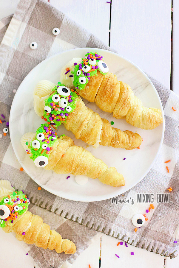 Overhead shot of puff pastry Halloween horns filled with cream on plate