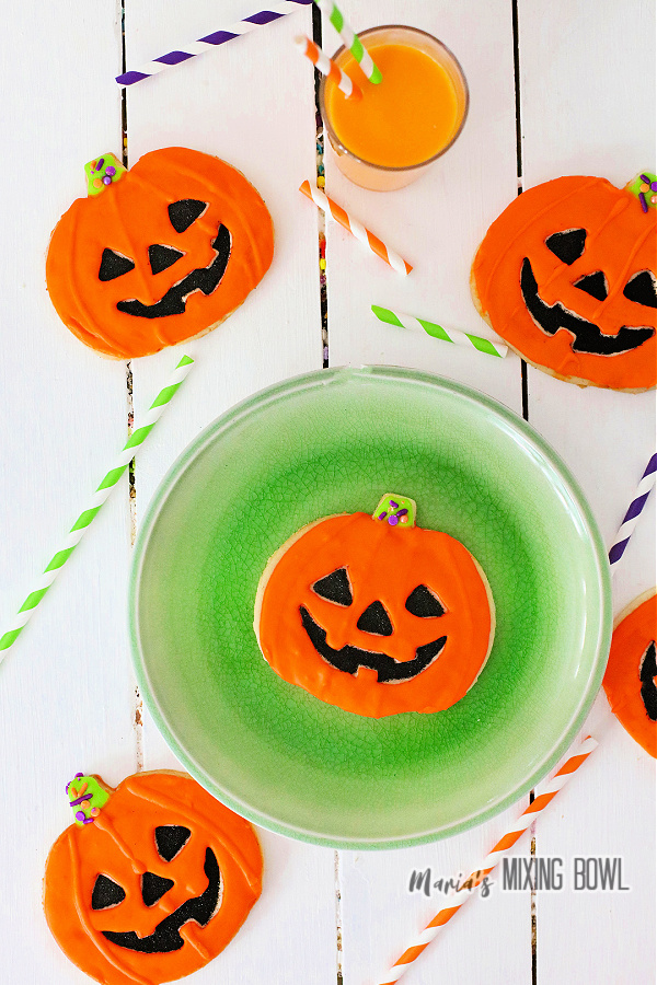 Overhead shot of jack-o-lantern cookies surrounding plate with another cookie