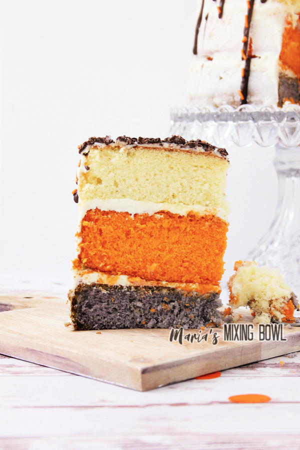 Slice of pumpkin spice latte cake with more cake on cake stand in background