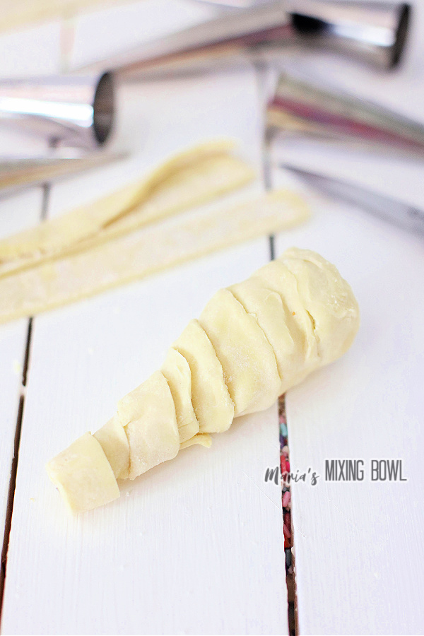 Pastry strips wrapped into Halloween horn