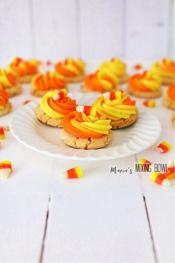 Candy corn cookies on white plate with more cookies in background.