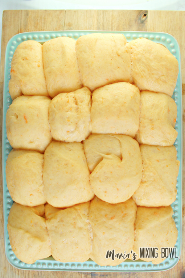 Overhead shot of sweet potato dinner rolls on green serving plate