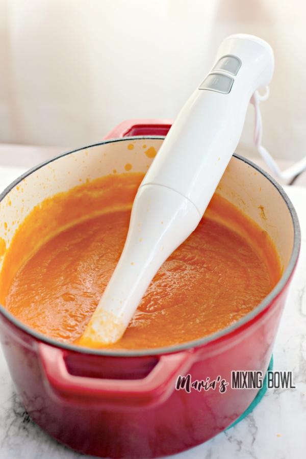 Immersion blender sitting in pot of easy butternut squash soup
